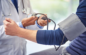 healthcare provider taking blood pressure of client