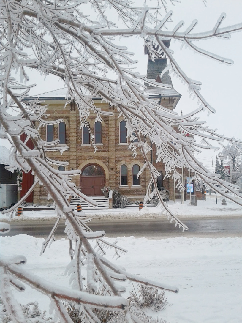 snowy image of old town hall red brick building with tree branches covered in ice