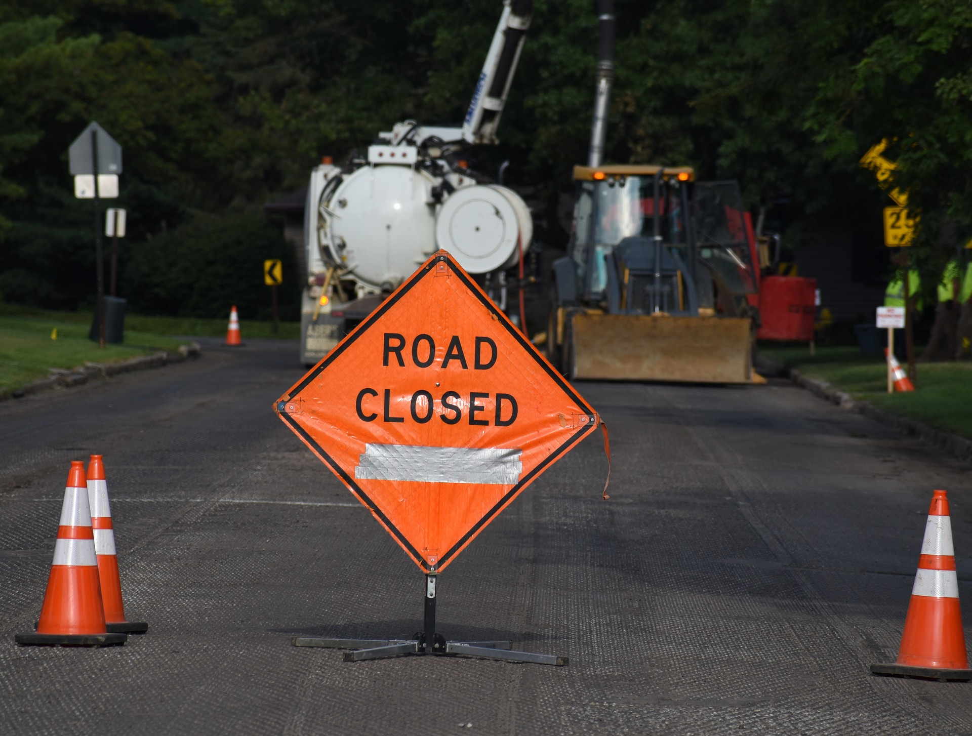 road closed sign with heavy equipment in background of picture