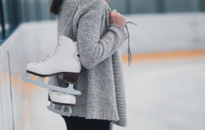 woman holding a pair of skates over her shoulder