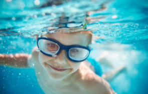 Boy swimming in pool underwater with blue goggles